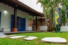 Jardim de casa de praia em Guaecá, São Sebastião, com prancha e churrasqueira