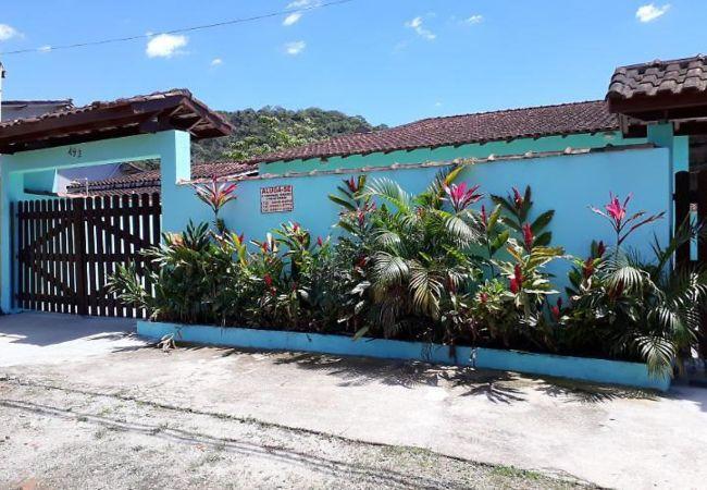 Fachada da casa em Ubatuba, com muro azul, jardins e portões de madeira