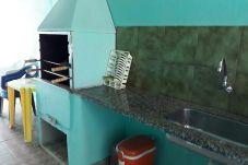 Vista da área da churrasqueira, com mesa de plástico e balcão de granito com pia