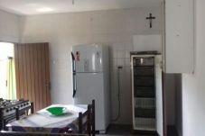 Vista da cozinha da casa, com fogão, mesa de jantar, geladeira, freezer e armário
