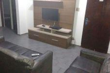 Sala com dois sofás, rack e Smart TV fixada em painel