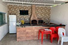 Vista da churrasqueira com forno e fogão a lenha, mesas e cadeiras de plástico, balcão, geladeira e Smart TV