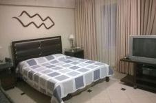 Quarto: cama queen com mesas de cabeceira e abajures à esquerda, móvel com TV à direita