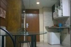 Cozinha: armário com micro-ondas, pia e frigobar à direita, porta ao centro, guarda-roupa à esquerda