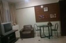 Sala: móvel com TV à esquerda, poltrona ao centro e mesa de vidro com duas cadeiras à direita