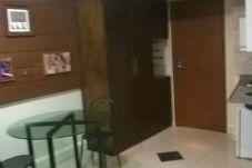 Mesa de jantar à esquerda, guarda-roupa ao centro e porta à direita
